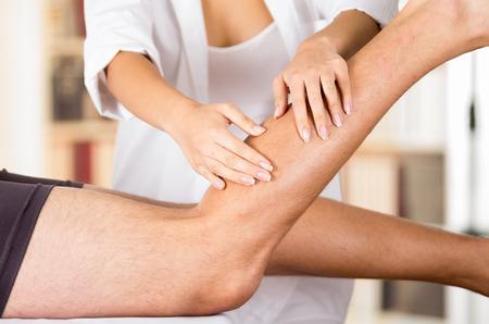 Gros plan femmes mains physio thérapeute travaillant sur les patients de sexe masculin jambes, floue clinique fond.