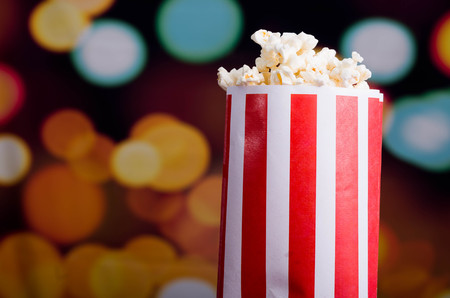 Closeup red white striped container standing up with popcorn reaching over edge, low angle, flashy vivid lights background. Stock Photo
