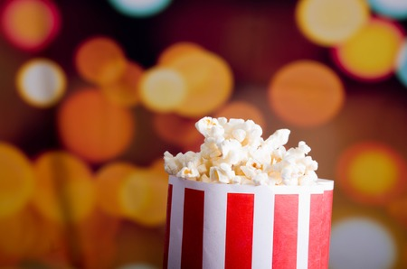 over the edge: Closeup red white striped container standing up with popcorn reaching over edge, low angle, flashy vivid lights background. Stock Photo