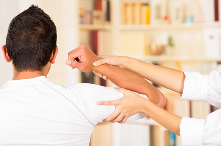 Female physio therapist and man seen from behind, helping patient stretch arm behind head, blurry clinic background. Stock Photo