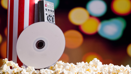 flashy: Closeup red white striped container standing up with popcorn lying around, dvd disc and remote control leaning on box, low angle, flashy vivid lights background.
