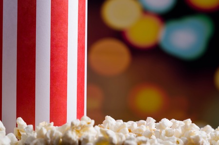 flashy: Closeup red white striped container standing up with popcorn lying around, low angle, flashy vivid lights background.