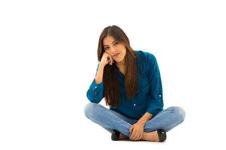 comfortable: Brunette model wearing casual clothes sitting comfortable on white background smiling to camera. Stock Photo