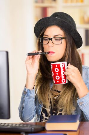 book jacket: Female brunette hipster type wearing glasses, hat and denim jacket sitting down by table with book while smoking e-cigarette, holding red coffee mug.
