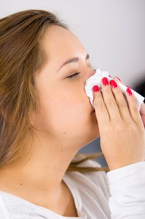 knocked out: Headshot profile brunette sick with the flu blowing her nose. Stock Photo