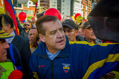 opposition: Quito, Ecuador - April 7, 2016: Closeup opposition leader Andres Paez surrounded by people, police and journalists during anti government protests in Shyris Avenue.