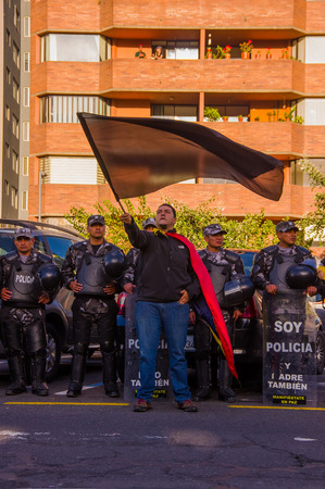misuse: Quito, Ecuador - April 7, 2016: Protester waving flag standing in front of riot police overlooking peaceful anti government protests, Shyriz Avenue.