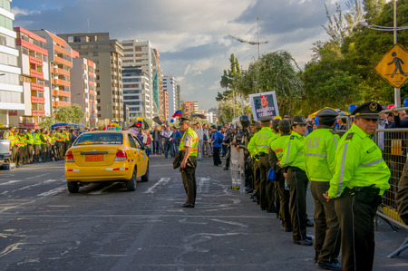 ecuadorian: Quito, Ecuador - April 7, 2016: Police awaiting overlooking peaceful anti government protests in Shyriz Avenue, beautiful blue sky and buildings background. Editorial