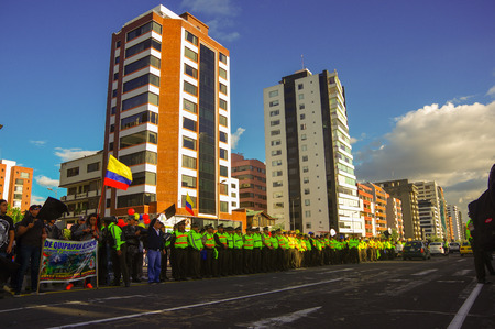 misuse: Quito, Ecuador - April 7, 2016: Police awaiting overlooking peaceful anti government protests in Shyriz Avenue, beautiful blue sky and buildings background. Editorial