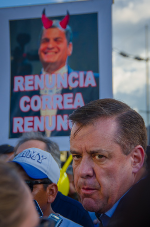 riots: Quito, Ecuador - April 7, 2016: Closeup opposition leader Andres Paez surrounded by people, police and journalists during anti government protests in Shyris Avenue.
