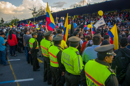 riots: Quito, Ecuador - April 7, 2016: Police awaiting overlooking peaceful anti government protests in Shyris Avenue, beautiful blue sky and buildings background.