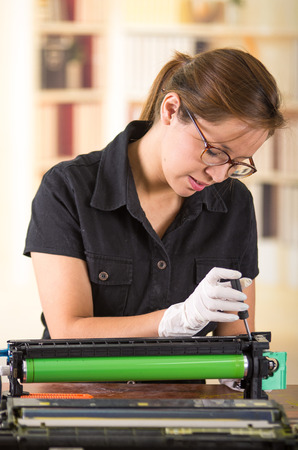 xerox: Young woman wearing black shirt performing toner change and printer maintenance, concentrated facial expressions.