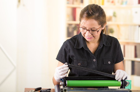 toner: Young woman wearing black shirt performing toner change and printer maintenance, concentrated facial expressions.