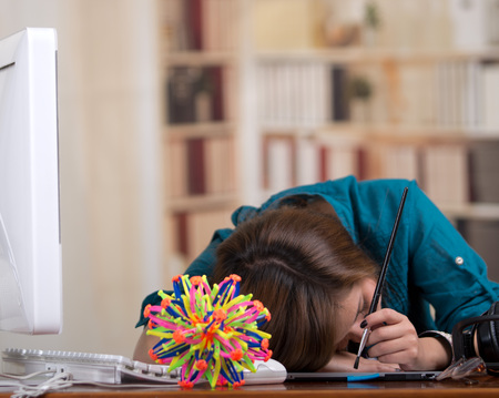 model kit: Brunette woman sleeping at desk with computer and molecular model kit on table. Stock Photo