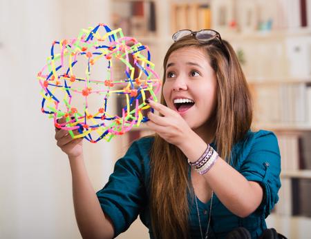 model kit: Brunette woman sitting by desk holding up molecular model kit and smiling.