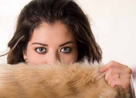 facing on camera: Headshot attractive brunette facing camera covering half her face with brown fur clothing, white studio background. Stock Photo