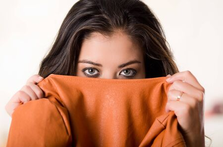 facing to camera: Headshot attractive brunette facing camera covering half her face with orange clothing, white studio background.