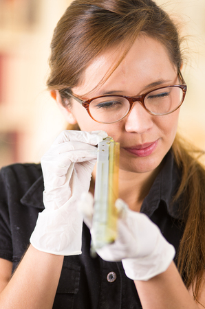 xerox: Young woman wearing black shirt holding up toner parts and looking closely into it while performing maintenance, concentrated facial expressions. Stock Photo