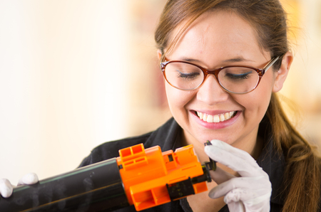 toner: Young woman wearing black shirt performing toner change and printer maintenance, positive attitude smiling.