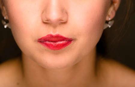 boca cerrada: mujer joven de cerca cerrados boca con lápiz labial rojo. Foto de archivo
