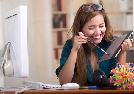 model kit: Brunette woman sitting by desk holding digital drawing tablet, molecular model kit on table and smiling.