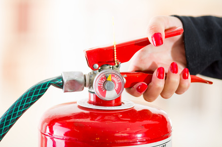 Closeup woman hands with red nailpolish showing how to operate fire extinguisher. Stock Photo