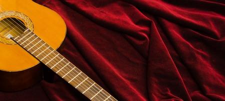 nylon string: Classical nylon guitar lying on red velvet textile, artistic instrument presentation. Stock Photo