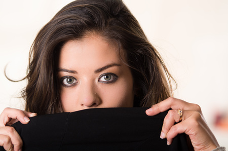 facing to camera: Headshot attractive brunette facing camera covering half her face with black clothing, white studio background.