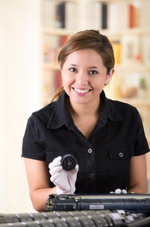 xerox: Young woman wearing black shirt performing toner change and printer maintenance, positive attitude smiling.