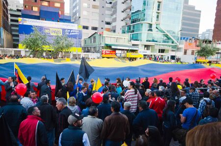 protest signs: Quito, Ecuador - April 7, 2016: Group of people displaying a very big Ecuadorian Flag, protest signs, and journalists during anti government protests in Shyris Avenue Editorial