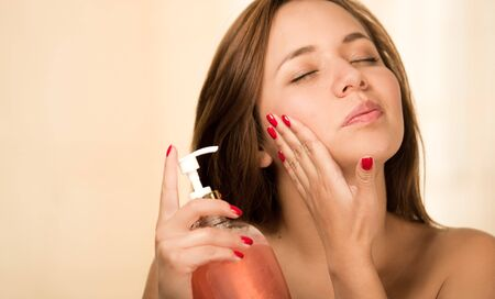 renewed: Young woman happily applying cream to bare skin neck, upper chest and face with eyes closed.