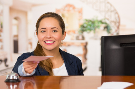 hotel receptionist: Young brunette hotel receptionist with friendly smile handing over key to client across desk, customers point of view. Stock Photo