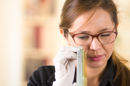toner: Young woman wearing black shirt holding up toner parts and looking closely into it while performing maintenance, concentrated facial expressions. Stock Photo