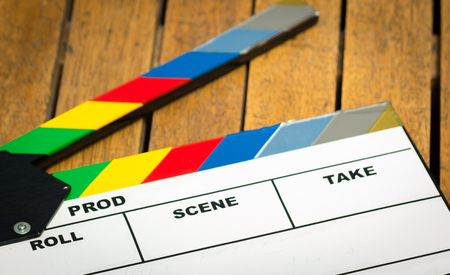 out of production: Colorful movie clapboard lying on wooden surface as seen from above. Stock Photo