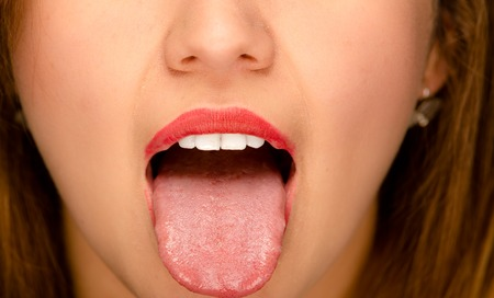 Closeup young womans open mouth with tongue sticking out.