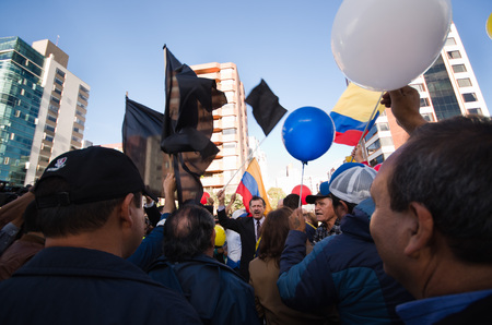 riots: Quito, Ecuador - April 7, 2016: Group of people Holding protest signs, balloons with police and journalists during anti government protests in Shyris Avenue.