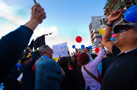 protest signs: Quito, Ecuador - April 7, 2016: Group of people Holding protest signs, balloons with police and journalists during anti government protests in Shyris Avenue.