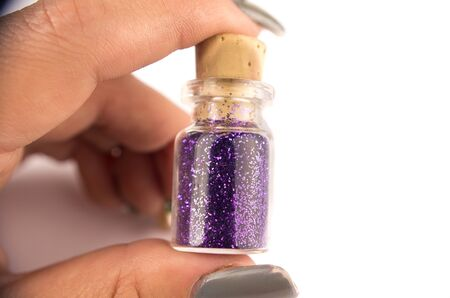 fingers on top: Closeup fingers holding up small bottle container with purple nail color inside and cork top on white surface. Stock Photo