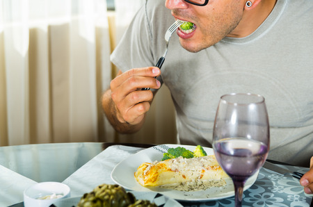 cooked pepper ball: Man sitting by classy dinner setting eating fork with broccoli, crepe covered in white sauce lying on plate.