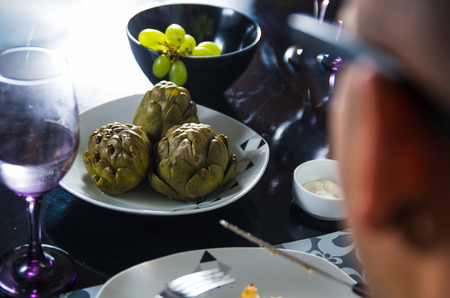 cooked pepper ball: Classy dinner table setting, cooked artichokes sitting in middle next to green grapes, left side of mans head and glasses visible.