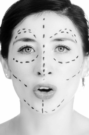 looking into camera: Closeup headshot caucasian woman with dotted lines drawn around face looking into camera, preparing cosmetic surgery, black white edition.