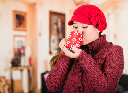 sip: Pretty young brunette woman wearing red sweater and beenie, taking a sip from cup of hot beverage. Stock Photo