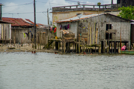 guayaquil: Muisne, Ecuador - March 16, 2016: Slums in poor section of the city, in the coast of Ecuador, with houses on poles over the sea water Editorial