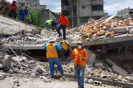 Quito, Ecuador - abril 17, 2016: Casa destruida por un terremoto con el equipo de rescate y maquinaria pesada en la parte sur de la ciudad.