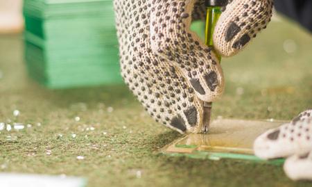 glasswork: Closeup hand wearing white working glove using handheld cutting engravement tool for glass.