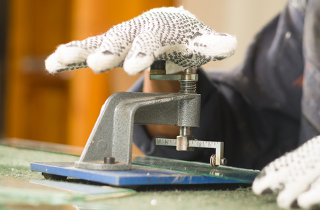 glasswork: Closeup hand wearing white working glove using pressure cutting device on piece of glass.