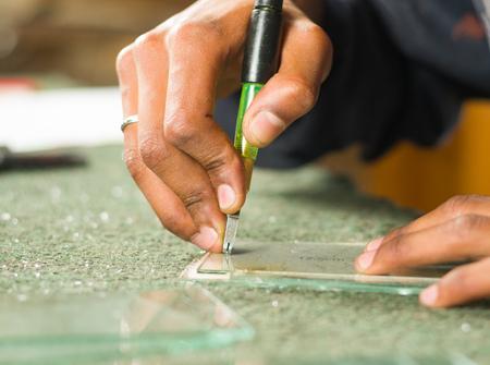 glasswork: Closeup hand using handheld cutting engravement tool for glass.
