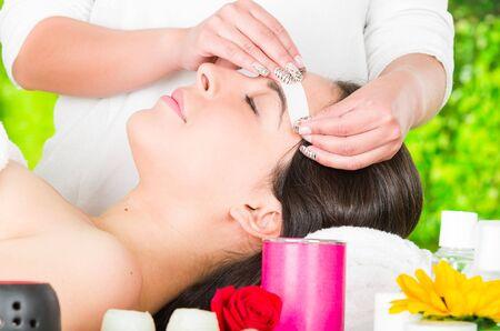 facial hair: Closeup womans face receiving facial hair wax treatment, beauty and fashion concept.