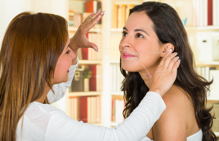 Cosmetologist performing facial hair removal using threading technique on brunette patient smiling. Stock Photo