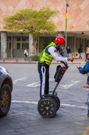 casco rojo: Cuenca, Ecuador - April 22, 2015: Policeman wearing red helmet on segway during city patrol duty.